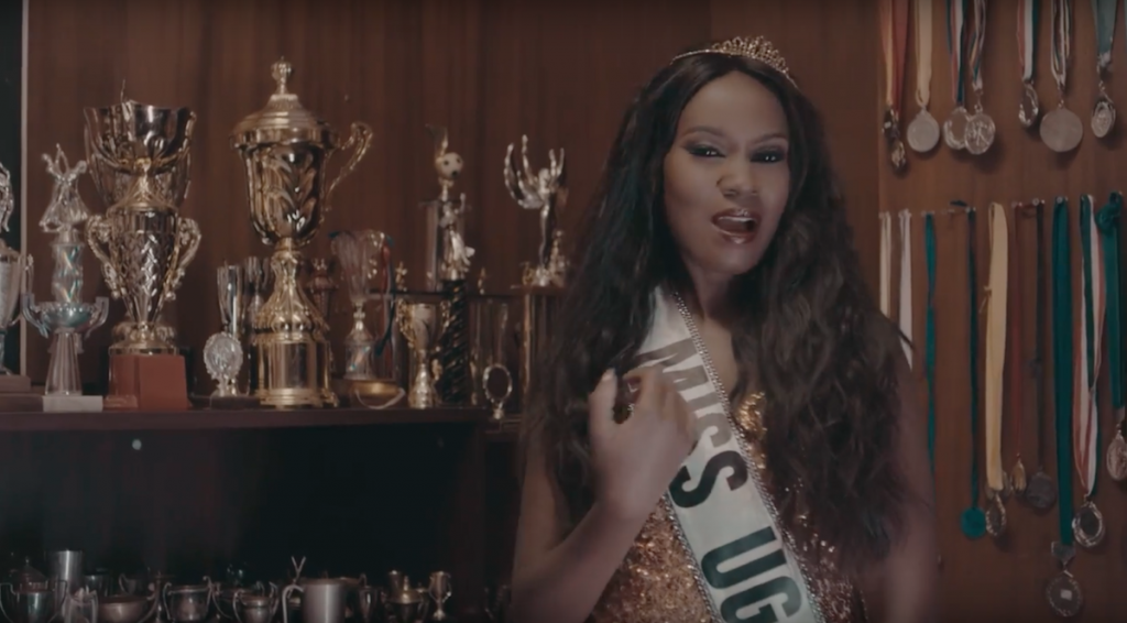 Juliana Standing infront of trophies with a Miss Uganda ribbon in Im Still Here Video - Spur Magazine