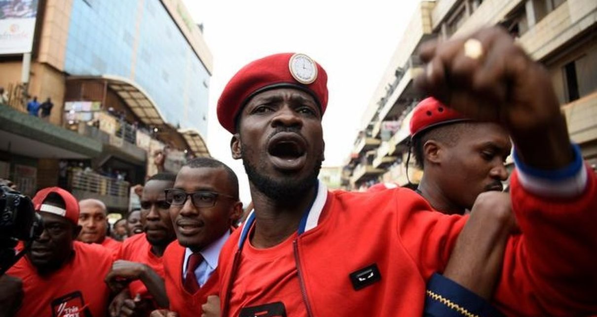 Bobi Wine, dressed in a red jacket and cap, shakes his fist in front.